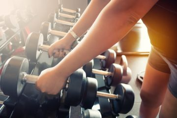 Close up of lady selecting weights from a rack in a gym