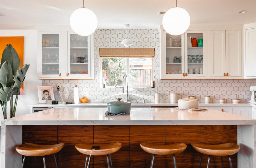 Stylish white and wood clean kitchen island with bar stools